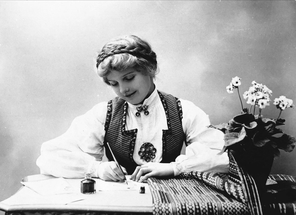 Studioportrett av kvinne i drakt med oppsatt hår. Hun sitter ved et bord og skriver et brev med penn og blekk. På bordet er det duk og blomsterpotte.