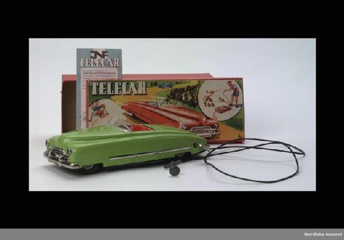 """Huvudliggaren: """"Leksaksbil, 'Telecar' av grönmålad plåt med gummihjul, de främre svängbara med ratt; fjädermekanism, hastigheten inställbar med växelspak; lös vindruta av plast, skruvnyckel, manövertråd i fjäderspiral med handtag, tryckt bruksanvisning på tyska, kartong med lock. Anv. av giv. vid början av 1950-talet. G. 13/9 1955 Studeranden Mikael Lagerqvist, Lidingö."""""""