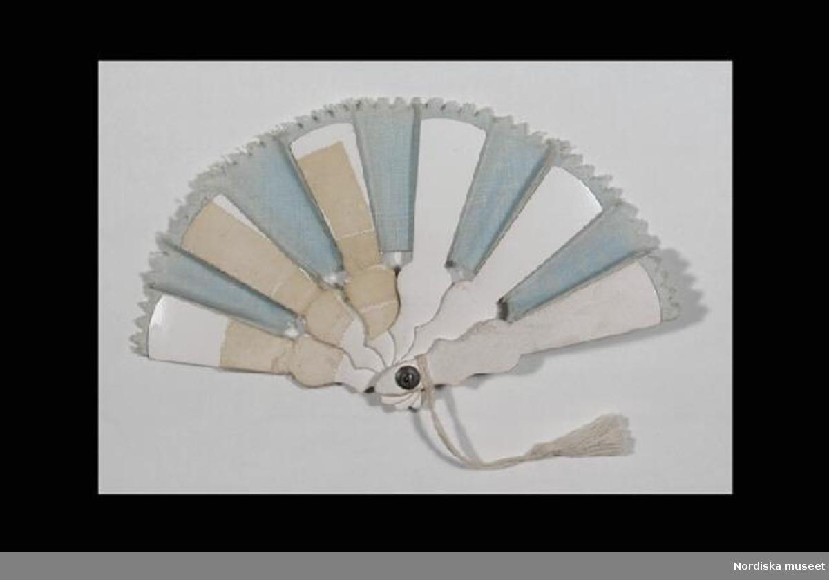 Inventering Sesam 1996-1999: (a) Damdocka, rörligt huvud m. sköld o halva armar av biskvi,  bruna blundögon av glas, öppen mun, målade ansiktsdrag, stoppad kropp klädd m. vit bomull. (b+) turnyr, svart o vitrandig bomull, spetskant, sex metallfjädrar, L 21,0 cm. + klänning, tvådelad, rosa ylle, svart spets, kjol m. tornyr, formsytt liv, skärp, Liv L 15 cm, Kjol L 33 cm. + underkjol, vit bomull, volang m. spets, L 26 cm. + underkjol, randvävd vit bomull, lagt veck, spetskant, L 27 cm. + hatt, ljusbeige siden, rosa spets, Diam 11,0 cm. + livstycke, virkat vitt bomullsgarn, rosa sidenband, sju vita knappar, L 12 cm. + lintyg, vit bomull, spetskant, L 24 cm. + benkläder, vit randvävd bomull, L 19 cm. + ett par strumpor, stickat vitt- och rödrandigt bomullsgarn, L 12 cm. + ett par knäppkängor m. klack (en saknas), svart skinn, L 6,5 cm. (c+) kappa o mössa, rosa-lila ylle, formsydd, 12 knappar av gulmetall, grönt yllefoder, pillerburks- formad mössa, stjärnformad  gulmetalldekor., rött yllefoder, L 34 cm. (d+) muff, svart päls, röda snoddar, brunt bomullband, L 8 cm. (e+) pälsjacka och mössa av vit päls, rött jackfoder, mössa m. blått sidenfoder, L 20 cm. (f+) klänning, tredelad, mönstertryckt bomull, rosaflammig botten, blommor i rött o blått, kjol m. liten tornyr, liv m. dragsko i midjan, puffärm, krage o manchett av vit bomullsspets, skärp m. spänne av koppar o mässing, turkosblå pärlor, Liv L 15, Kjol 31 cm. (g+) klänning, tvådel., formsytt liv m. lång ärm, vit spetskrage, rosa sidenband runt ärmsluten, kjol av rosa linne klädd med vit glesvävd ylle, kantad m. vit bred bomullsspets, i midjan rosa sidenband med rosett, Liv L 15, Kjol 32 cm. (h) kofta/jacka, vit silkestrikå o grönt siden, kantspets av glaspärlor, lila bomullstrikåfoder, L 16 cm. (i) förkläde, rödrutigt tryckt bomullstyg, vit spets, knytband o dekorationer av vit bomull, L 30 cm. (j) förkläde, mönstervävd vit bomull, vit spets o randigt sidenband, L 34 cm. (k+) 2 st lintyg, vit bomull, spetskant, L 26 cm