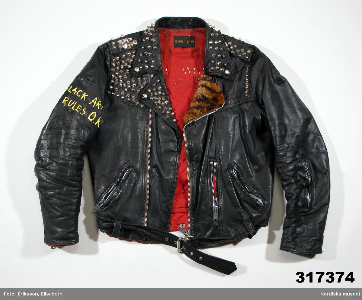 Jacka av svart skinn med blixtlåsknällning, fodrad med rött nylontyg. 1980-tal. Prydd med en mängd detaljer: nitar på bl a bakstyckets ok, axelklaffar o krage; säkerhetsnål på vänster axel; målad dödskalle över korslagda säkerhetsnålar; syntetpäls på vänster slag.