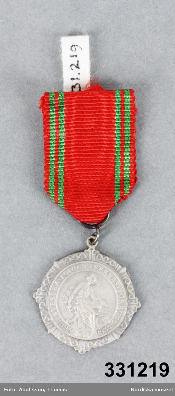 """Medalj i silver, rund. Åtsidan med motvi i relief av kvinna i romersk dräkt hållande i krans och kvist, text i omskrift """"SVENSKA FOTOGRAFERNAS FÖRBUND  omgiven av krans med SFF i monogram på flera ställen. frånsidan slät och med stämplar """"S&Co"""" / s:t Erik /  kattoft (tre kronor) / """"N9"""". Upptill på medaljen ögla vari ett rött sidenband med grön rand är fäst. Säkerhetsnål på baksidan av bandet. /Leif Wallin 2011-02-02"""