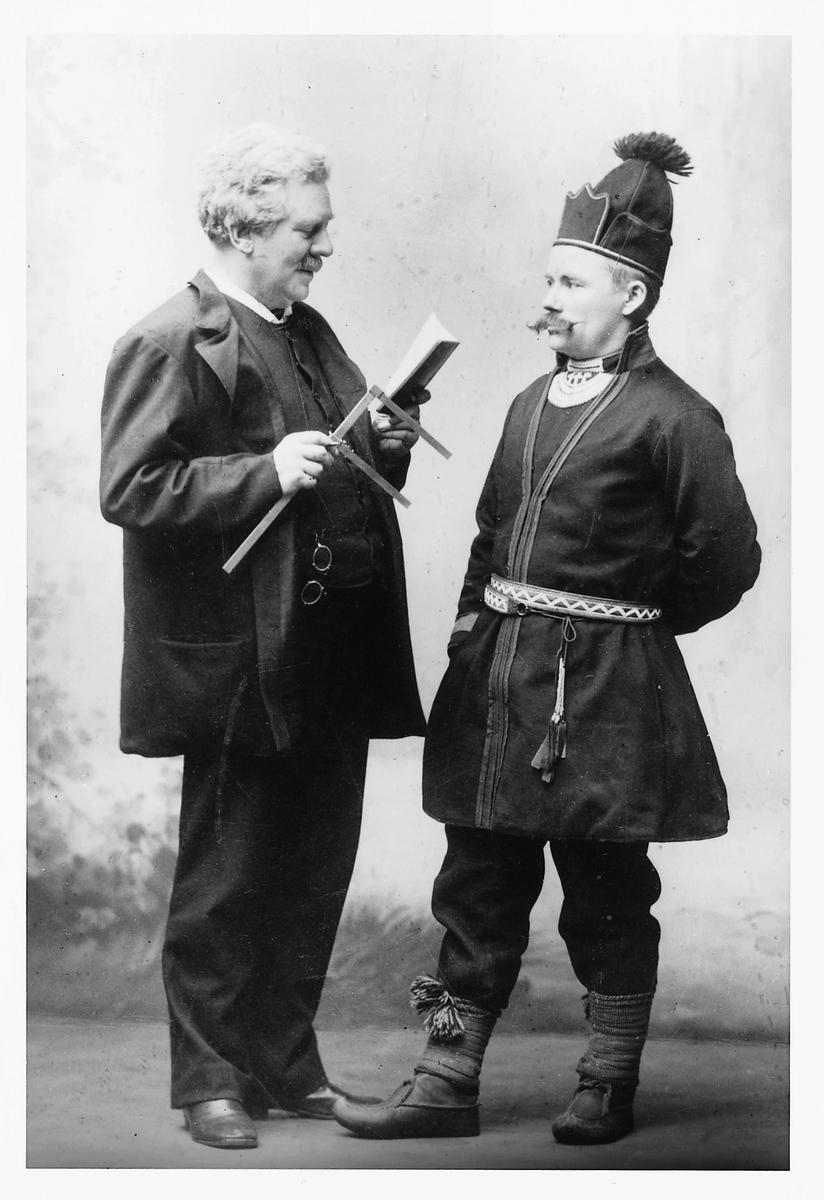 Antropologen Gustaf Retzius i färd med att mäta härjedalssamen Fjellstedts huvud, inom ramen för den rasbiologiska forskningen. Retzius till vänster i bild är klädd i kostym och håller ett skjutmått i ena handen medan han läser ur en bok. Framför honom står Fjellstedt iförd traditionell samisk dräkt.