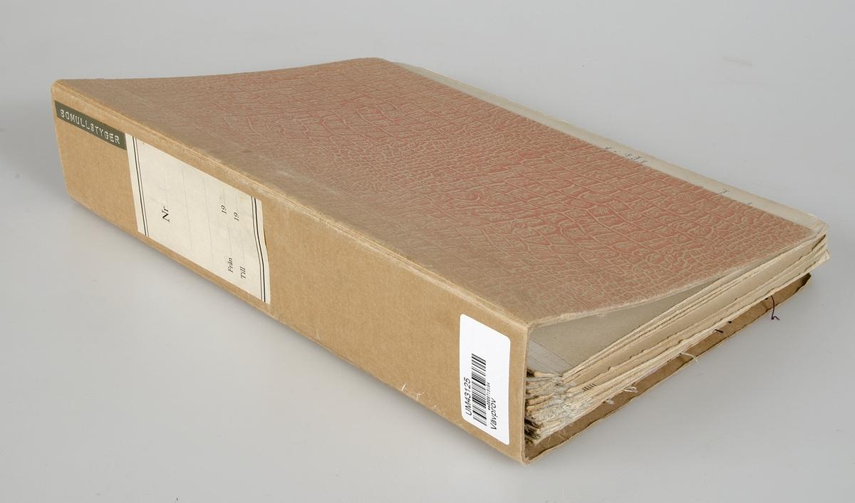 """Pärm med vävprov klistrade på pappskivor. Pärmen är märkt """"BOMULLSTYGER"""". Vid många av vävproven finns information om material och vävning. De flesta av vävproven är märkta med B-nummer och är förtecknade i liggaren """"KATALOG ÖVER NYTILLVERKNINGAR""""."""