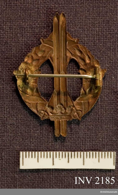 Samhörande nr är 2170-2188.Märke, skidlöpar-, brons, generalitet.Lagerkrans med tre kronor och ett par upprättstående skidor. Nål på baksidan för fastsättning. Märket erövrat av general Almgren.