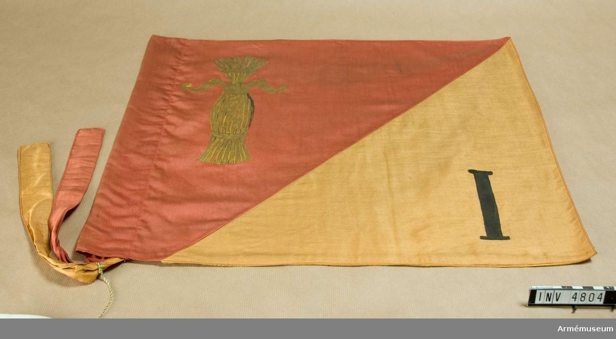 Mått: 540 x 440 mm.Wasa grenadjärbataljons s k riktflagga, Finland. Duken i  bomullssatin är tvärdelad med Övre delen röd och den undre  delen gul. Flaggan är sydd i dubbelt tyg, tryckt lika på båda  sidor. I det röda fältet visas Wasakärven och i det undre en  romersk I:a. Vid vänster sida en slå och band av tyget i rött  och gult för flaggans fästande vid stång.