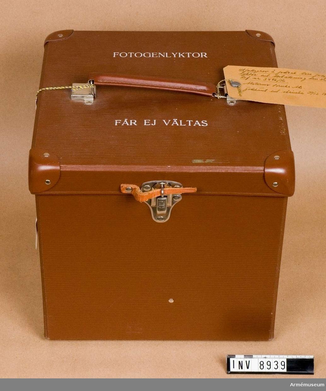 """Utfallsprov 1958. Av """"unikapapp"""". Utfallsprov å fodral till fotogenlykta enligt beställning  1958-11-25 Ref.nr 3486/56. Alstermo Bruks AB Godkänt enligt skrivelse 1958-12-30, blysigill märkt: KAIF med en krona. Lådan är försedd med bärhandtag, gångjärn och lås. Bestående av: 1 st fodral,  2 st lyktglas, 1 st tratt av plast, 1 st veke av väv.  Samhörande nr är AM.8939 - 8941"""