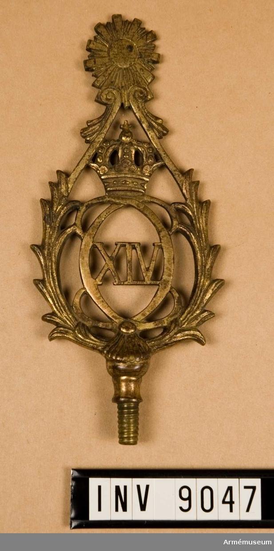 Spets t fana m/1819, infanteri och kårer. Av förgylld metall med konungens namnchiffer C XIV J omgivet av en bladkrans i spetsform.  Samhörande nr är 1932:3880, 1975:9046-47.