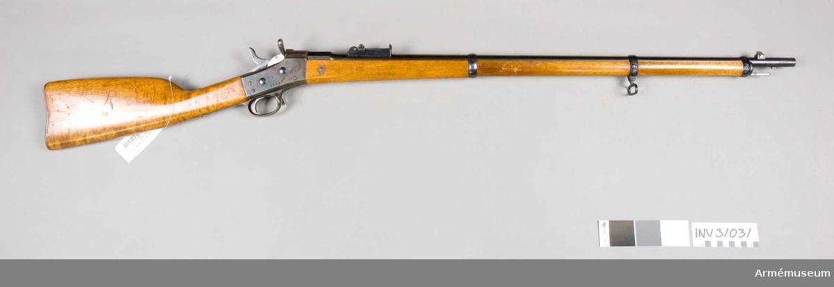 """Samhörande nr är 31031-31032, gevär, mynnings/kornskydd. Gevär. 1867 års fm 1889. Grupp E II. 1889 års senare försöksmodell, (andra försöksmodellen)  Mått: Antal räfflor 3 st, räffelstigning 1 varv på 28,8 cm. Laddning 4,7 g komprimerat svartkrut. Utgångshastighet 535 m. Kopparmantelkulans längd 30,7 cm, vikt  15,5 g.   Pipan är rund,  men har längst bak ett 3,75 cm långt, åttakantigt kammarstycke. På pipans översida 5,1 cm bakom mynningen sitter en kraftig kornklack, å vars översida det med stor fot försedda kornet är anbringat. Kornet är flyttbart i sidled genom en sorts tvärt genom kornklacken gående skruv. På pipans undersida 2,9 cm bakom mynningen finns en bajonettklack. Ramtrappiktet sitter  6,6 cm framför lådans främre ände. De tre """"trappstegen"""" äro avsedda för håll mellan 300 och 500 m, ramen för avstånd mellan för avstånd mellan 600 och 1 400 m, men för längre håll får man använda """"sidsiktet"""". Detta består här av en på löparens bak- eller översida anbringad liten, avlång skiva, med vinkel-  böjda ändar, som kan skjutas ut åt höger och vars rörelser begränsas av en skruv på löparens baksida, vilken skruv går i en urtagning på  skivan. I skivan finns en siktskåra, som som då skivan skjutes åt höger så mycket det går, kommer till till höger om siktramen. Graderingen å de sidsiktet avsedda avstånden, 1 500 - 2 400 m, finnes på rammen fram- eller undersida. I patronlägets bakände finns ej urfräsning för hylsflänsen, utan i stället är ett är ett särskilt  stycke, som är blånat och på pipans översida fästad med en skruv, infällt i pipans bakände. Detta stycke går litet nedanför patronlägrets övre kant i pipans bakplanet, är där omkring 0,7 cm brett och har på detta nedre parti urfräsning för hylsranden. På kammarstyckets översida står krönt C, på vänstra sidan numret 14123.  Mekanismen är av Remingtons system och liknar m/1867-1874. Lådan och varbygeln äro gråhärdade, slutstycket och hanen blanka. Slutstycket har centralantänding, rätt långt, ganska smalt handtag """