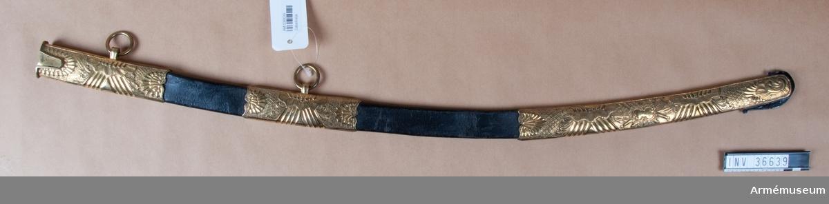 Grupp D II. Baljan är klädd med svart läder och har släpsko, mittbeslag och munbleck av kraftigt ciselerad, förgylld mässing. De båda sista beslagen har var sin koppelring.  Daterad till ca 1800.