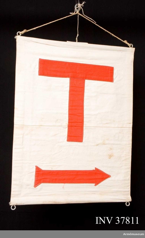 Grupp H I.  Sydd av vit dubbel väv med kanaler i båda kanter. Upp- och nedtill en järnten med vardera två öglor med snören för upphängning.  Påstickat på dukens båda sidor ett rött T och en röd pil.  M 7611-218010, f.d. Tc 29022.INV  år 1981.S.s. AM 6237-6241.