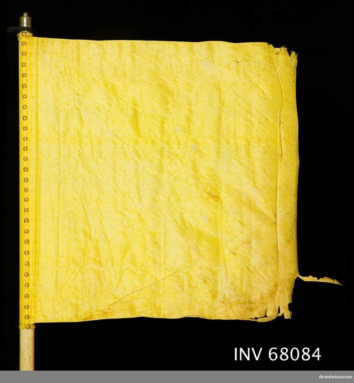 Duk: Tillverkad av enkel, gul sidentaft. Duken fäst med en rad tennlickor på ett gult band.  Dekor: Saknas.  Stång av trä, vitmålad, smal. Holk av mässing.   Skinremmar: En övre vit skinnrem fäst vid stången på 690-710 mm mätt från dukens nedre fäste, bildar en 320 mm lång ögla.   En nedre brun skinnrem fäst vid stången på 55-75 mm mätt från stångens nedre ände, bildar en 280 mm lång ögla.
