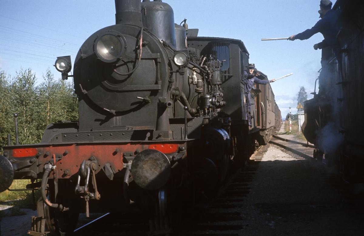 Kryssing mellom to godstog på Arneberg stasjon på Solørbanen. Lokomotivpersonalet utveksler aviser som er rullet opp på kosteskaft.