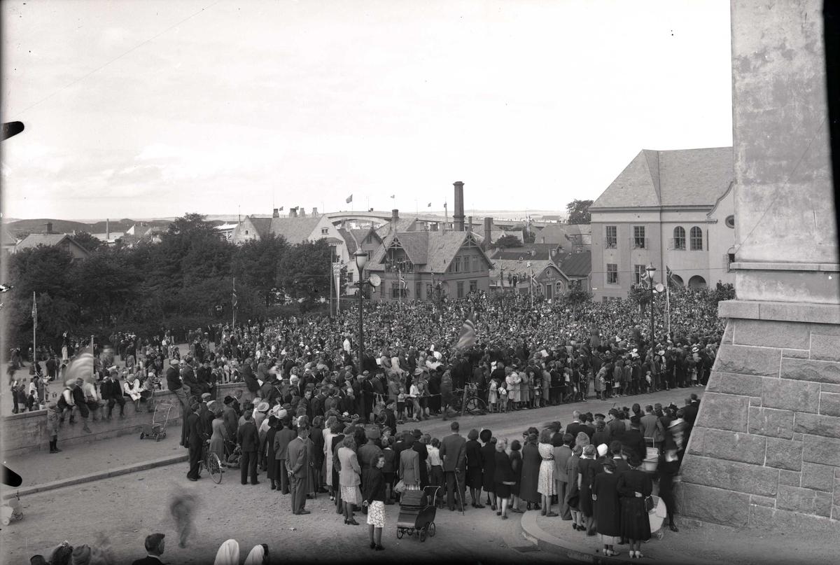 Stor folkemengde samlet foran Rådhuset. Gata er avsperret og folk står samlet bak tausperringene. I bakgrunnen til h. ses Festiviteten. Fra kong Haakon den 7.s besøk i Haugesund, 22.08.45.