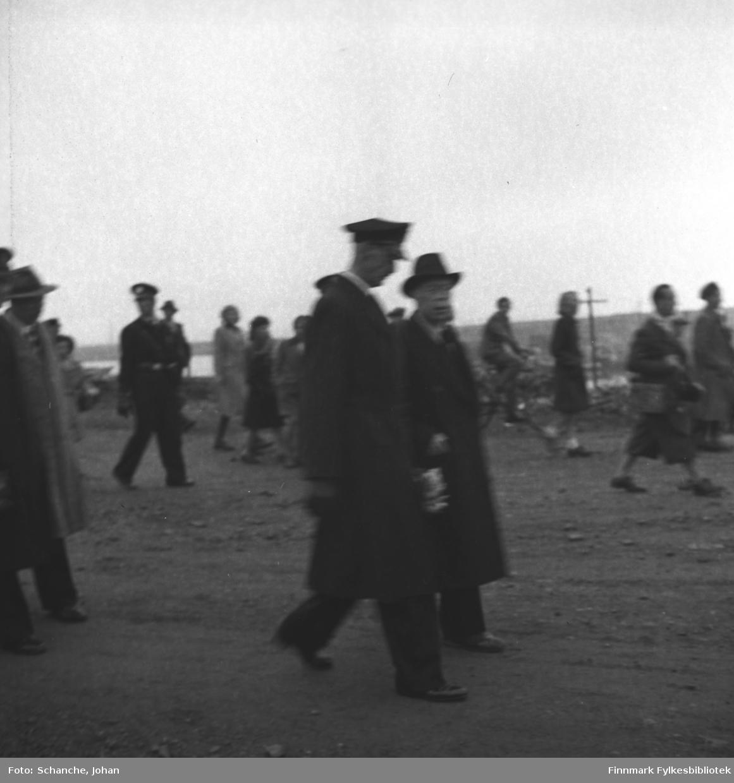 Kongebesøk i Vadsø: Kong Haakon VII og fylkesmann Hans Gabrielsen går på gata i Vadsø. Folkemengde har samlet seg langs veikanten, flagger. Byens sentrum ligger ennå i ruiner.