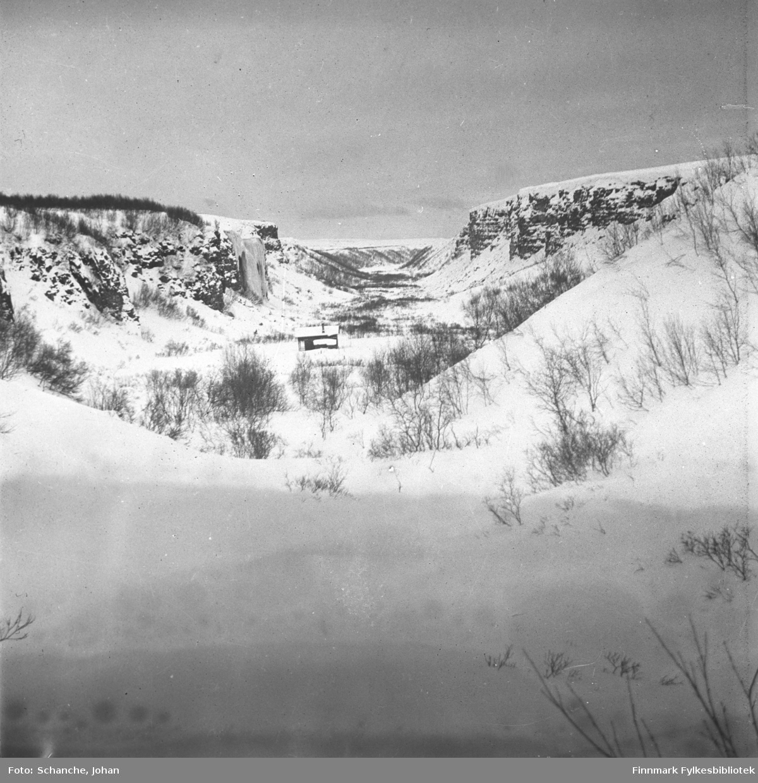 En hytte fotografert i Thomaselvdalen vinteren 1946. Bildet er tatt fra lang avstand. Dalen er dekt av snø.