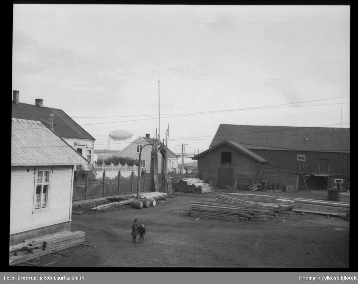 Luftskip forankret ved luftskipsmasta i Vadsø.  Bildet viser også bygningene i nederste del av Tollbodgaten. To barn står på gårdsplassen til Brodtkorbs trelastlager, i bakgrunnen ser vi tollboden.  Det er umulig å se hvilket luftskip som er fortøyet i masta, men vi gjetter at det er tatt ved samme anledning som FBib.98012-025.