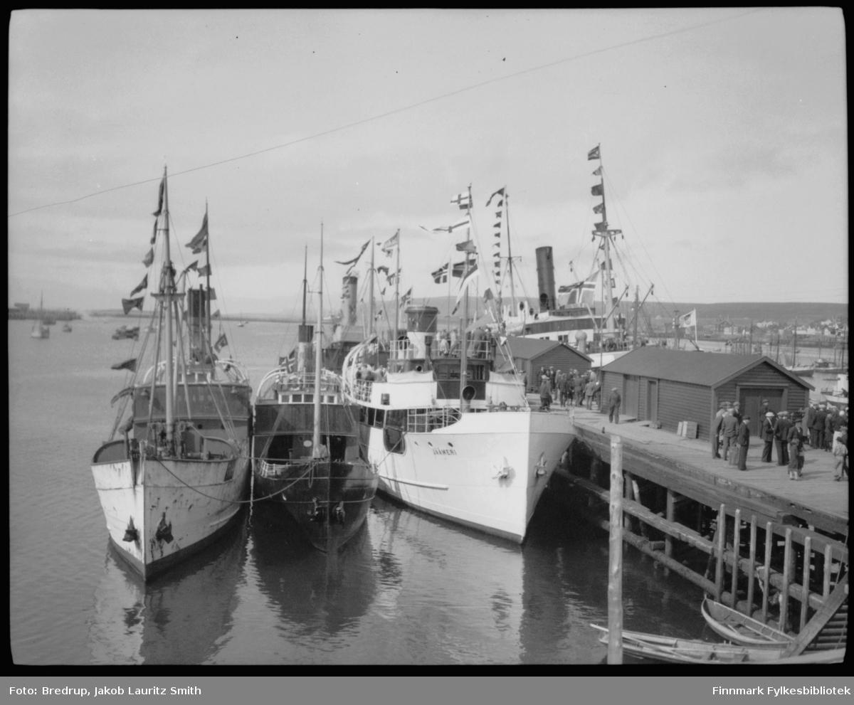 Byjubileet 1933 - Vadsøs 100-årsjubileum. Bredrups egne notater: 'Dampskibskaien søndag 23.7.33. 'Sanct Svithun', 'Pasvik', 'Jäämeri' og 2 norske agnbåter.  Båtene ligger ved kai, 'Jäämeri' ligger innerst, nærmest kamera.  Antar at de to ytterste båtene nærmest kamera er agnbåter.  Folk henger rundt på kaia og prater, mest menn