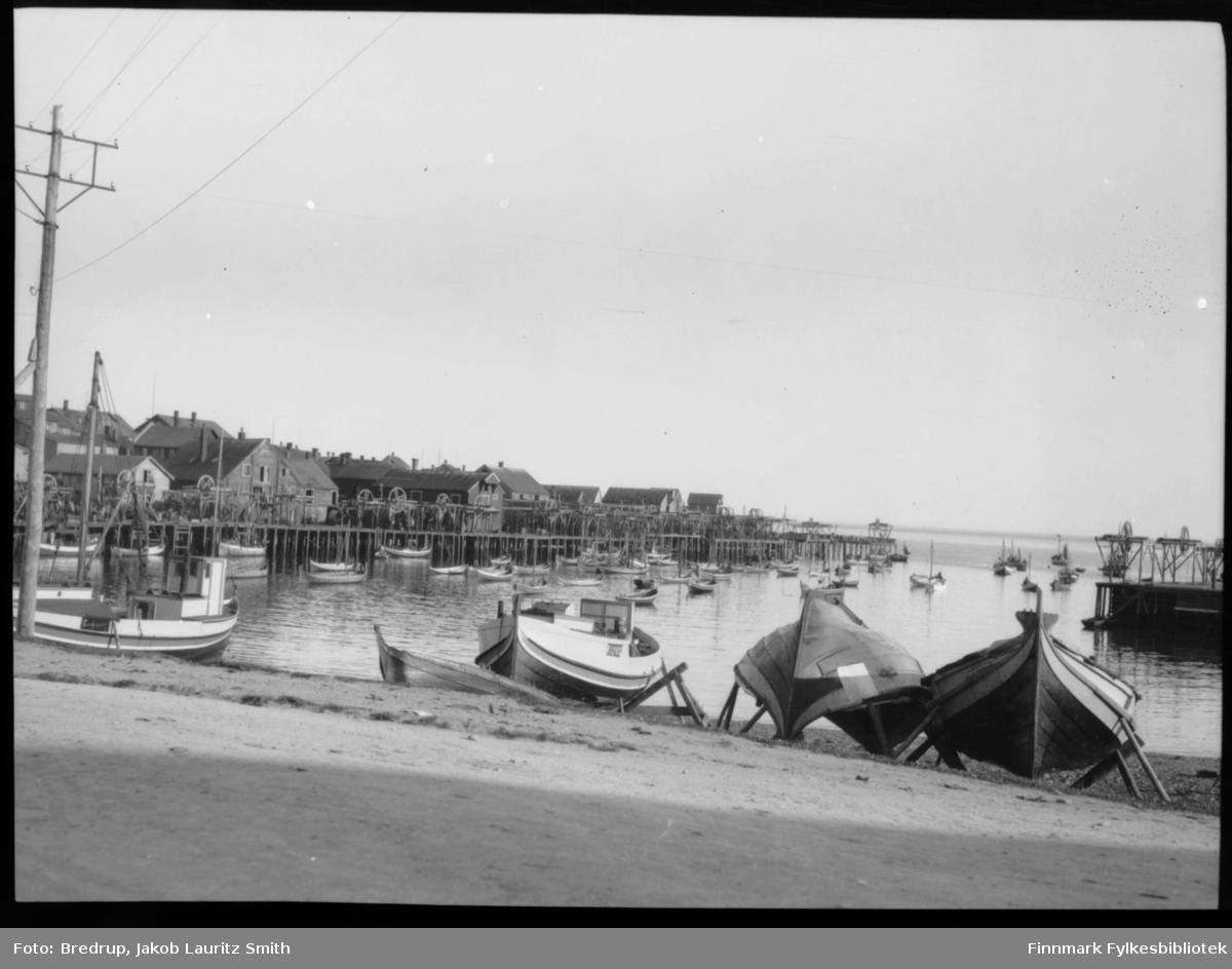 Båter trukket opp i fjæra, Valen i Vardø. Bildet er tatt fra Valen og utover havna. Vi ser kaier og pakkhus på rekke og rad, båter på havna.