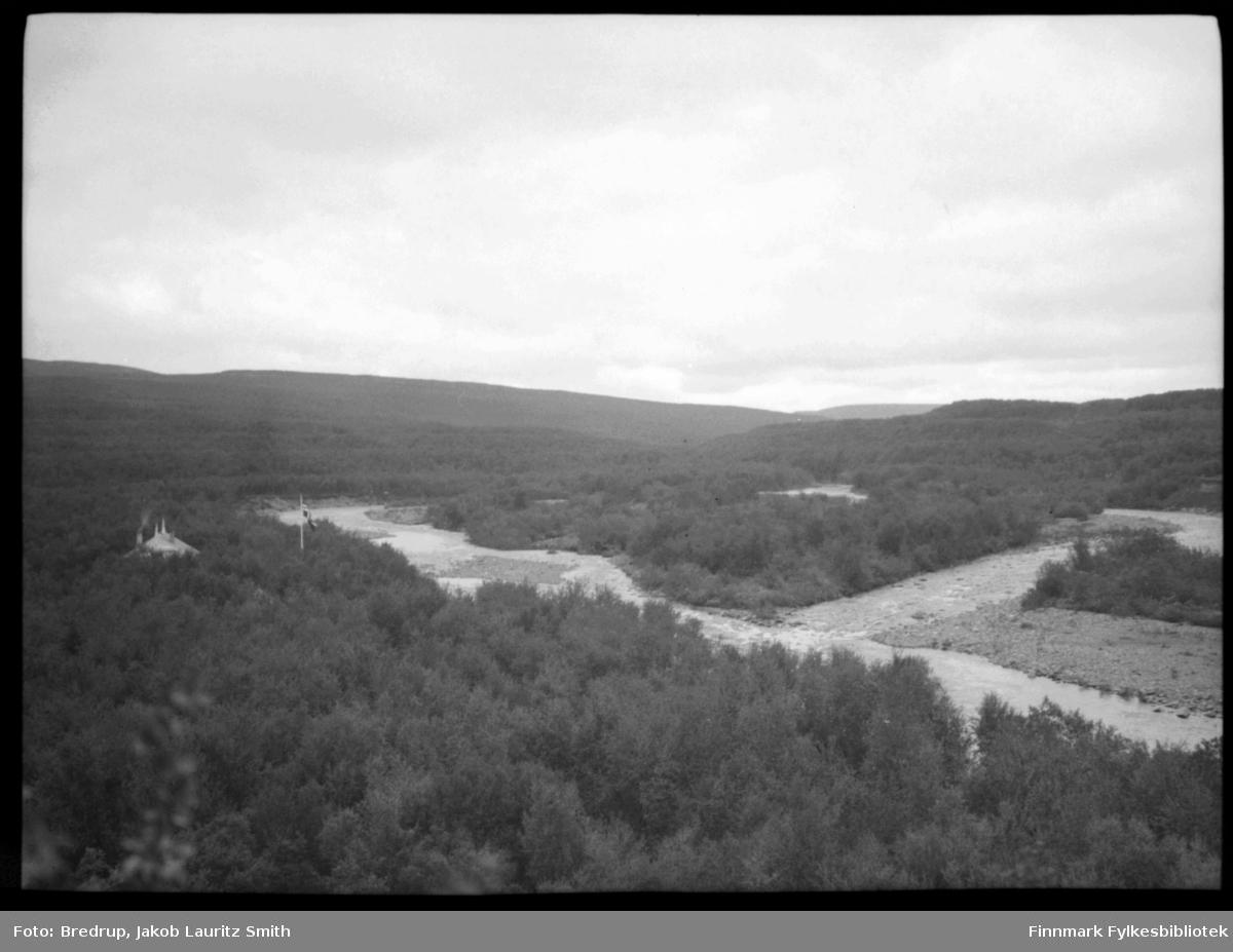 Naturbilde: Bildet er tatt fra en høyde ned mot ei elv som deler seg rundt en øy i elva.  Tett løvskog langs breddene.  På fotografens venstre elvebredd en bygning med røyk fra pipa.