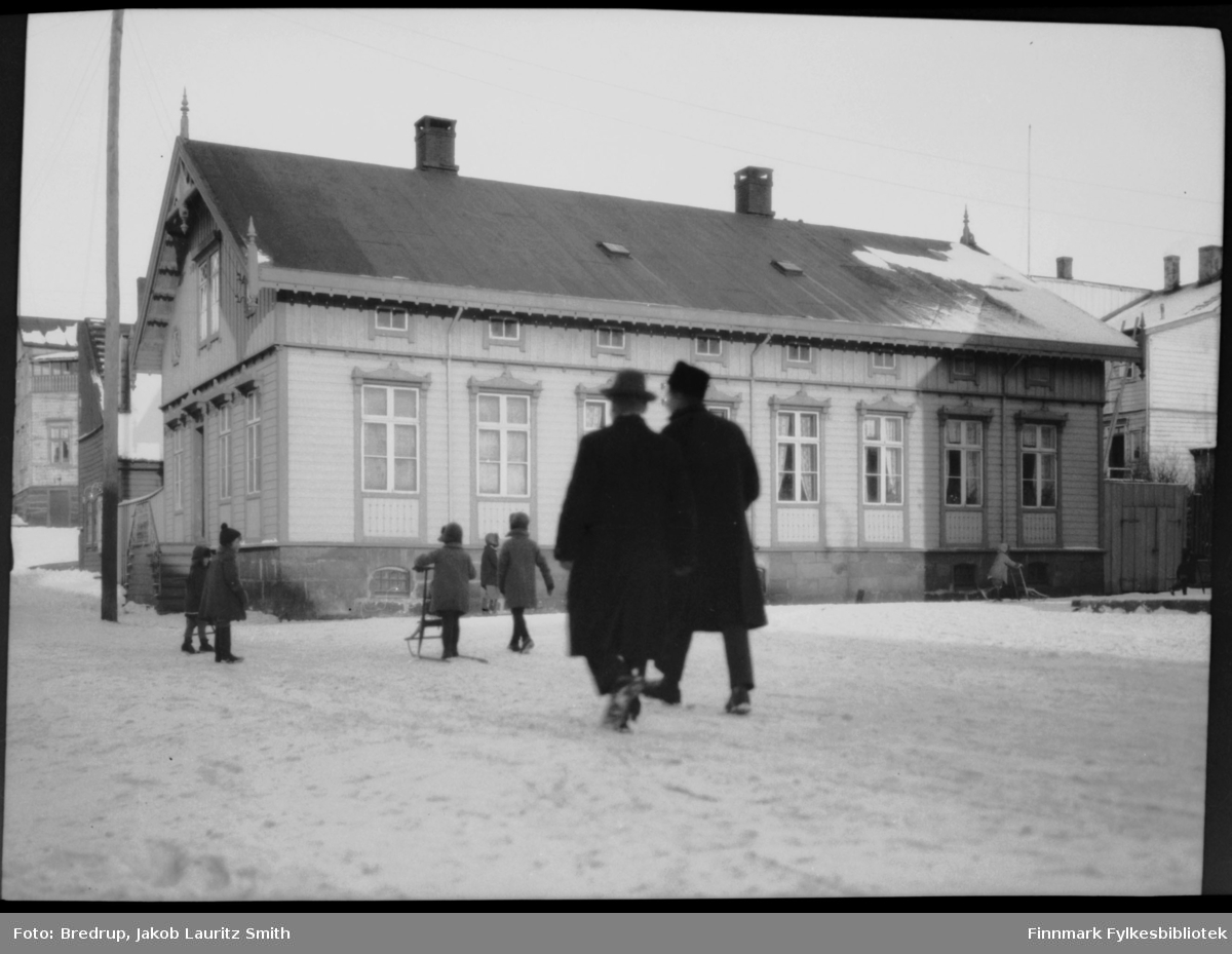 Vinterbilde fra torget i Vadsø.  Barn med spark, og to menn spaserer oppover Tollbodgaten.  Midt i bildet Brodtkorbgården.