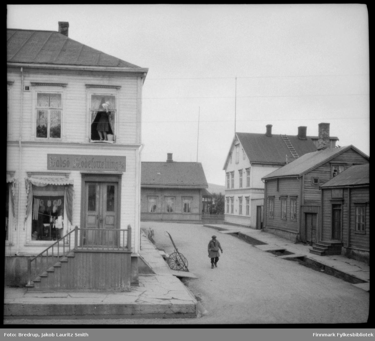 En enslig mann i samekofte går forbi 'Vadsø Modeforretning', drevet av søstrene Sundelin fra til krigen.  En kvinne står i andre etasje og pusser vinduer. Det står en sykkel og ei kjerre parkert utenfor butikken.  Ellers er flere bygninger med på bildet.