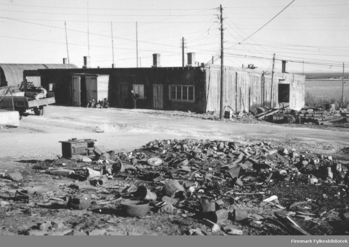 Ruiner i Vadsø sentrum etter andre verdenskrig. I forgrunnen en haug med diverse objekter i metall og andre materialer. Til venstre i ruinhaugen står en stekeovn. Lenger til venstre og bakover i bildet ser vi bakparten på en lastebil som kjører forbi, og bak der igjen står skallet av en bygning, omgitt av stolper med elektrisitetslinjer imellom. Til venstre i bakgrunnen kan man også se en del av en brakke med avrundet tak