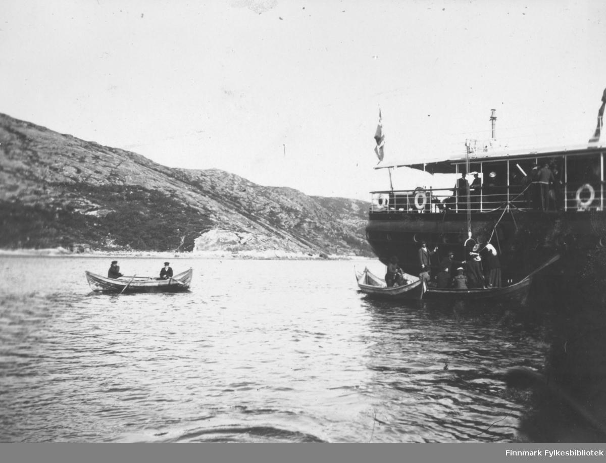 Flere robåter rundt et større dampskip på en fjord eller elv. Skipet ser ut til å være et turistskip?