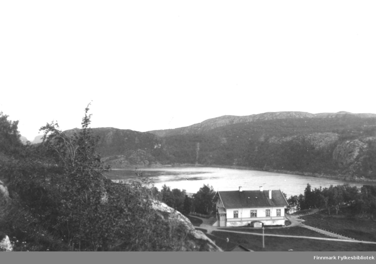 En lys bygning ligger ved en fjord eller et vann