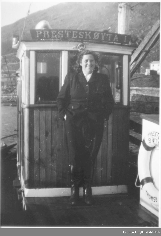 """Kvinne fotografert ombord på """"Presteskøyta I"""". Båten var en av tre presteskøyter i Finnmark. Dette er den første av tre båter. En av våre kontakter mener at dette kan være tatt i Smalfjordi 1950-årene og han husker at denne kom til Skjånes da han gikk på internatskole der. På den tiden var Berlevåg, Gamvik kommune i Tana Prestegjeld. Navnet på kvinnen er ukjent.   Jfr. flere opplysninger om presteskøytene her:  https://digitaltmuseum.org/011012802391/presteskoyta-i-masoy-1949-1969-baten-var-en-av-tre-prestskoyter-i-finnmark?i=3&aq=owner%3A%22MKG%22+classification%3A%22480%22&slide=0"""