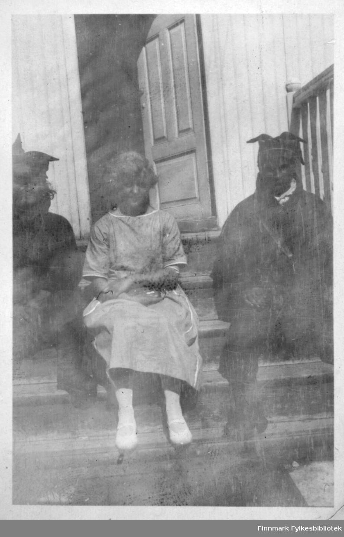 Gruppebilde på trapp. To samiske menn sitter på hver side av ei jente