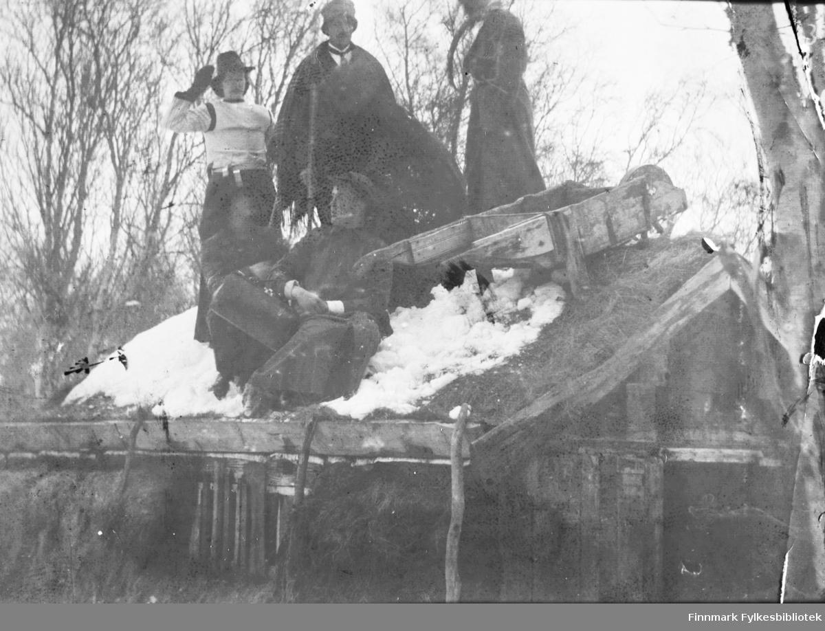 Ungdommelig tull i Tana, ca. 1916. Personene på bildet har kledd seg ut og dratt en trillebår opp på et tak, der de har blitt fotografert