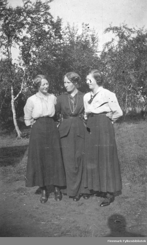 Tre damer poserer foran fotografen en solfylt sommerdag i august 1916. Alle tre er pyntet i fine klær