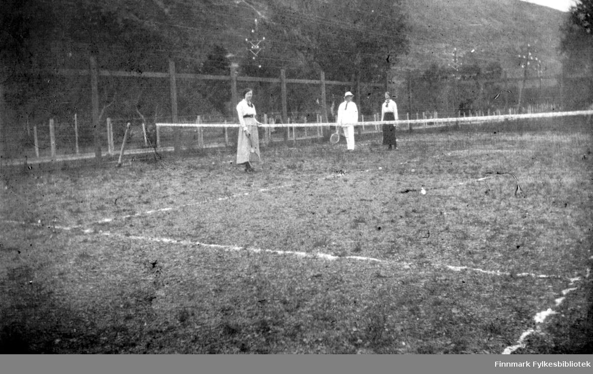 To damer og en mann spiller tennis. Damene er kledd i skjørt mens mannen har på seg hvit dress og matchende hatt. I bakgrunnen er det gjerder av forskjellige slag, samt stolper med telefon- eller kraftledninger.
