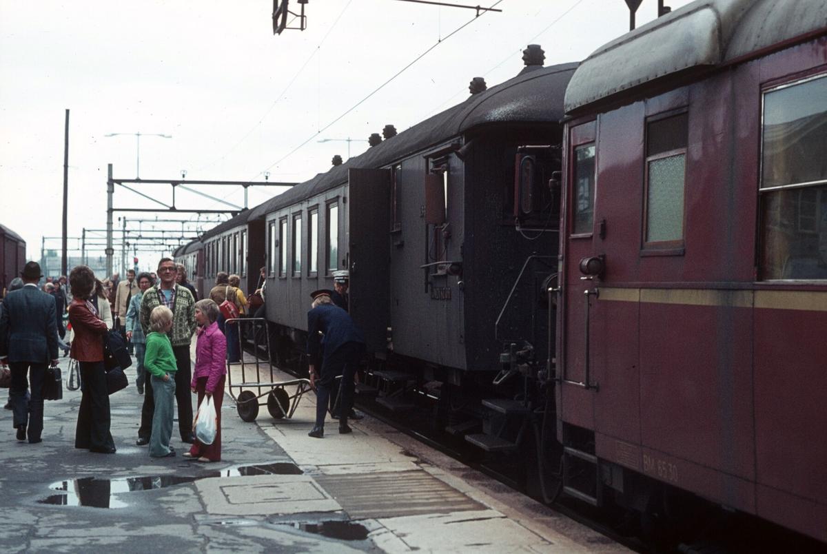 Ski stasjon. Lokaltog med motorvognsett type 65 fra Oslo Ø har ankommet. Reise- og ekspressgods blir losset ut av reisegodsvognen, BFS 65.