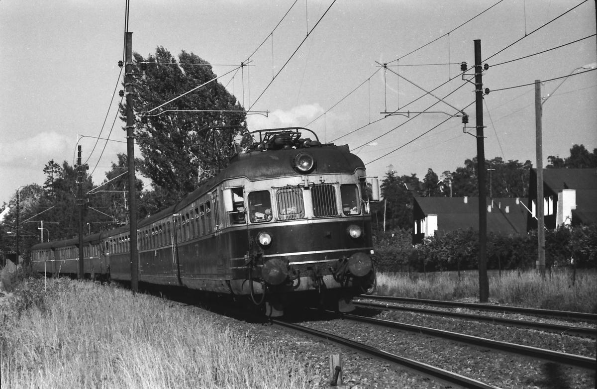 Hurtigtog 811 Oslo V - Larvik med NSB elektrisk ekspresstog type 66 passerer Strand. BM 66 01. Bakerste togsettet, type 68A, ble koblet fra i Drammen og gikk til Vestfossen.