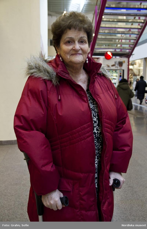 Foton tagna av elever från Mediagymnasiet i Nacka. Eleverna fick i uppdrag att  till Nordiska museets webbplats om kläder och mode leverera bilder från vardagen i Stockholm under ett par veckor i februari 2011. Dam med kryckor som promenerade i Skärholmens centrum med sin man.