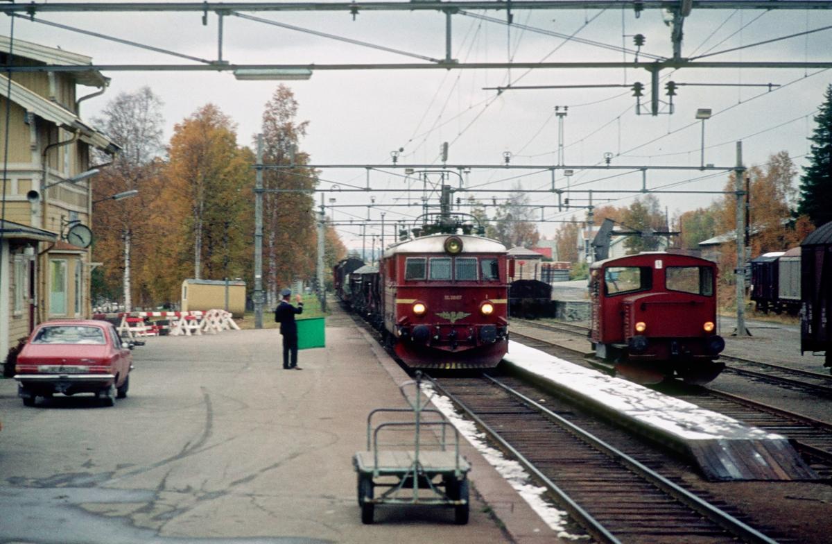 """Raufoss stasjon. Togekspeditøren viser signal """"Passer"""" til godstog med El 11 2087. I spor 2 står en skinnetraktor type 214 som har kommet med kipptog fra Gjøvik."""