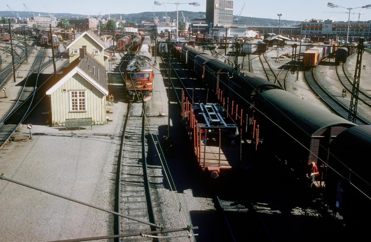 Filipstad skiftestasjon. Stillverksbygning, togspor, skiftespor og lastespor. Godstog med NSB elektrisk lokomotiv type El 8.