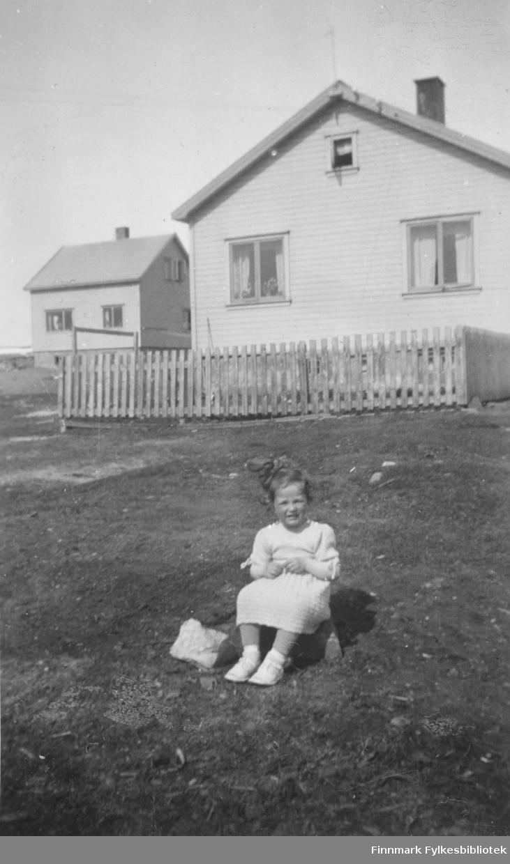 Torill Ebeltoft fotografert utenfor familiens hus, i 1953. Hun har fin sommerkjole og sløyfe i håret. I bakgrunnen ser vi andre hus i området Fosseveien - Engstien
