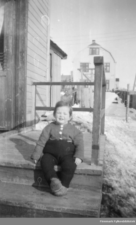 Torill Ebeltoft på trappa hjemme hos bestemor og bestefar Kvam i Slettengata, ca. 1952. I bakgrunnen ser vi andre boliger i området