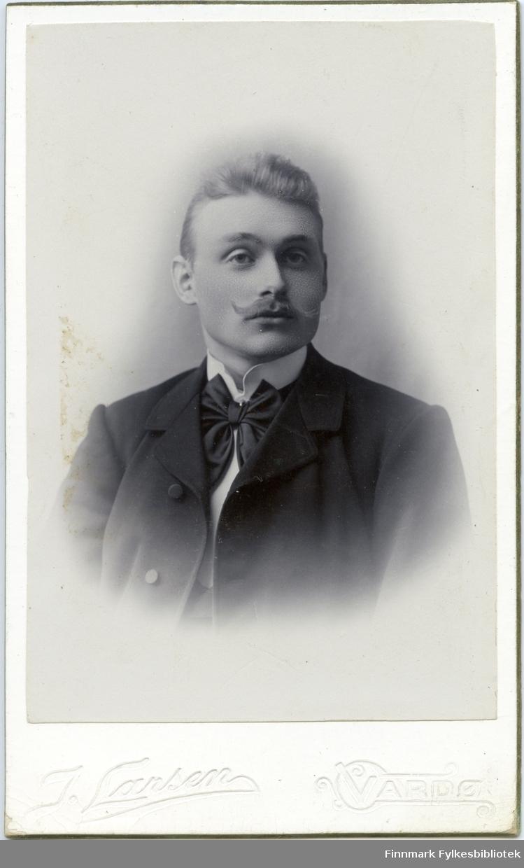 Visitkort. Halvkroppsportrett fra en mann, kanskje samme mannen som i fb.96012-007, Peder Nicholaisen. Han er kledd i dress og har en fin sløyfe på halsen.
