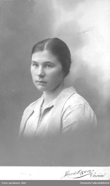 Portrett av en ung kvinne, kledd i en lys bluse eller kjole, fotografert i fotoatelier. Navn ukjent.