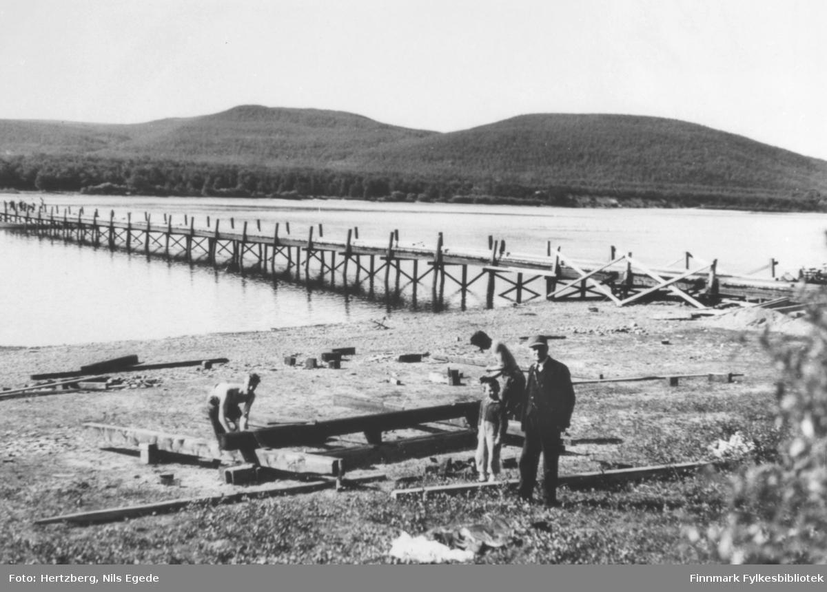 Oversiktsfotografi av brubygging over Tanaelven i Seida. Løytnant Tapio i forgrunnen til høyre, et barn og to menn med bruen i bakgrunnen.