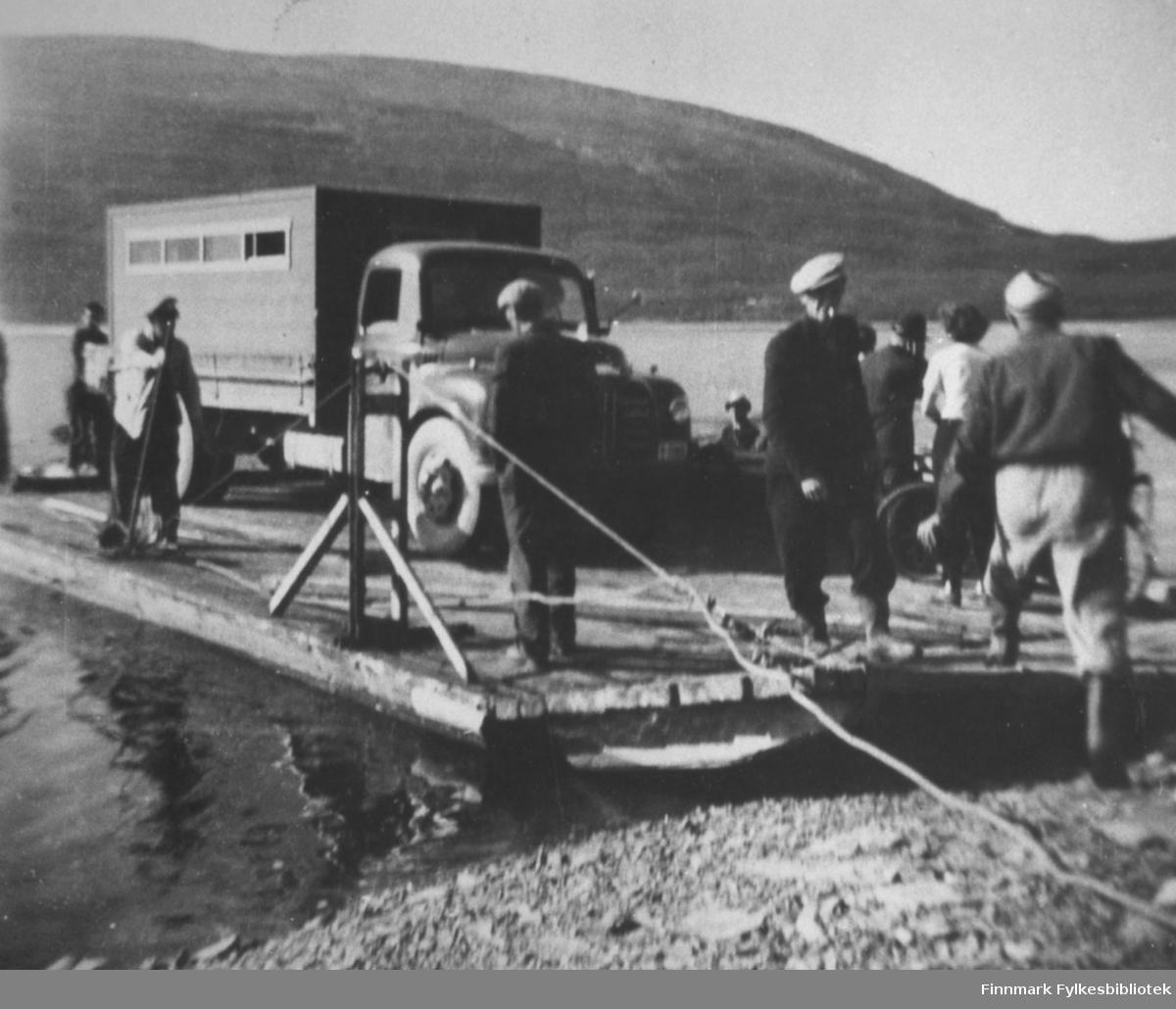 På ferge over Tanaelva ved Langnes. Hjemtur fra Kongsfjordfjellet. På bildet ser man ferga med en lastebil og noen menneskrer ombord.