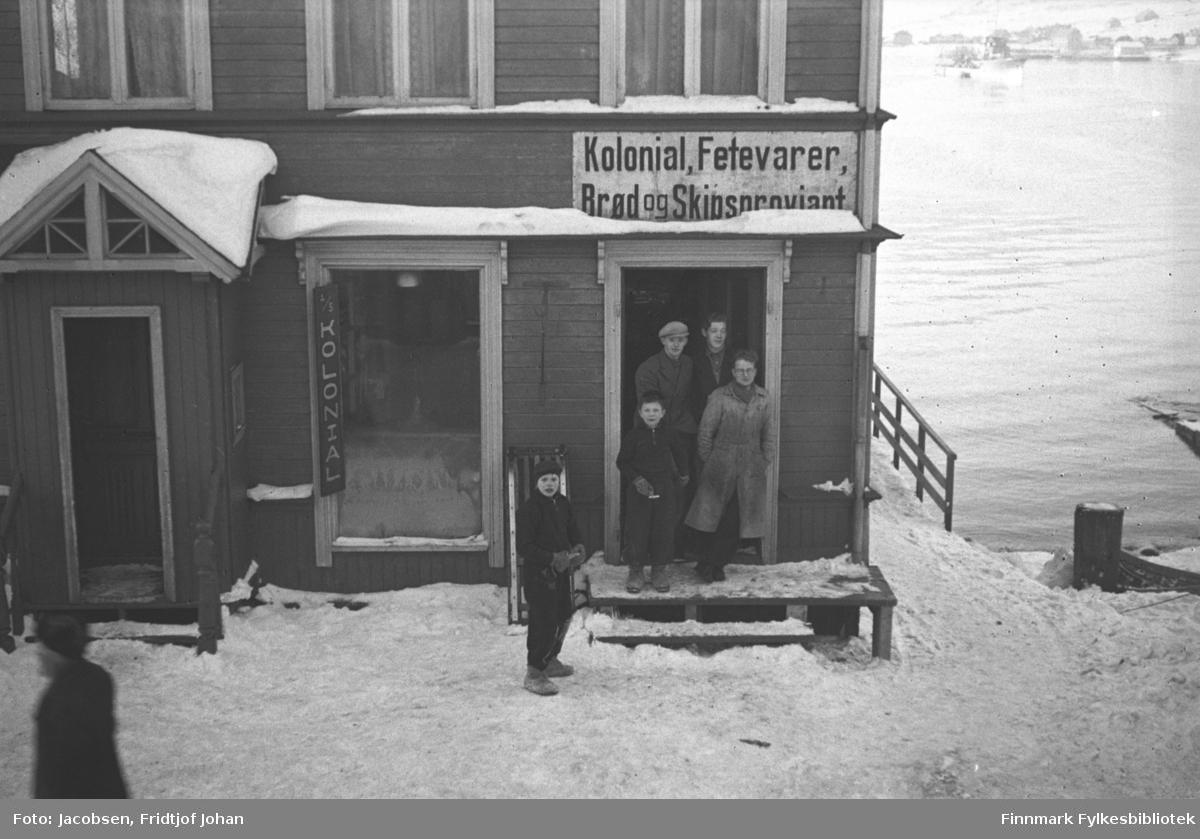 Kristian Johnsens kolonial- og skipsproviant ved havna i Hammerfest. I døra, bak fra venstre, står: Breivik, ukjent fornavn, Gunnar Høidal, og foran til høyre står John Strand. De to guttene er ukjente. Butikken har en liten trapp/platt foran og et vindfang helt til venstre på bildet. Et lite rekkverk står på kaikanten av kaia, til høyre og på andre siden av den blikkstille havna ses et snødekt Fuglenes.