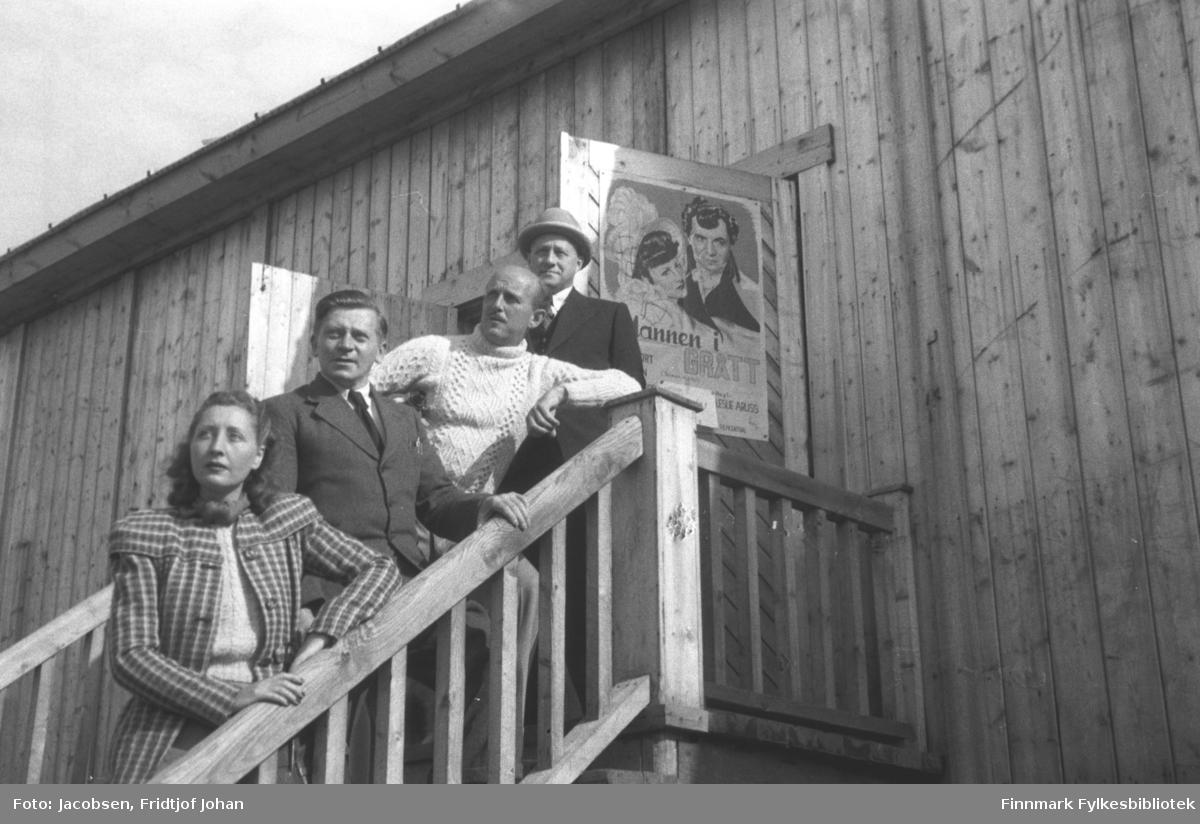 Kinobygget i Hammerfest. Fire mennesker står på trappa og dobbeltdøra med en kinoplakat står åpen bak dem. Damen nederst, iført en rutet jakke og lys ullgenser, og mannen i hvit strikkegenser er venner av Aase og Fridtjof fra telegrafskole-tiden. Mannen som står som nr. to fra venstre er kinobestyrer Erling Jensen. Han er iført ganske mørk dress med hvit skjorte og slips. Mannen bakerst i mørk dress og hatt på hodet er ukjent.