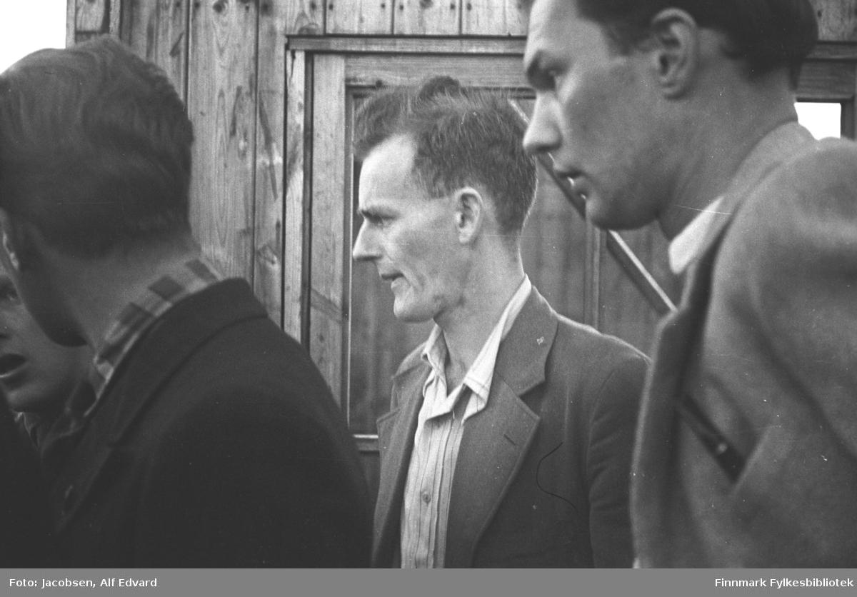 Flere menn følger ivrig med på bergingen av en havarert lastebil ved Storelvbrua i Hammerest. Helt til høyre på bildet står Alf Edvard Jacobsen. Han har en forholdsvis lys dressjakke på seg. En liten flik av den lyse skjortekragen ses foran i halsen. Han har en (fylle-?)penn i sin venstre brystlomme. Ved siden av han står Hans Svendsen. Han har en ganske mørk dressjakke og lys skjorte som er åpen i halsen. To ukjente menn står foran de dem. Mannnen nærmest kamera har en mørk jakke og kragen på en rutet skjorte ses rundt halsen hans. Bak dem står en brakke med stående, umalt panel. Et to-delt vindu står på veggen ved siden av Hans.
