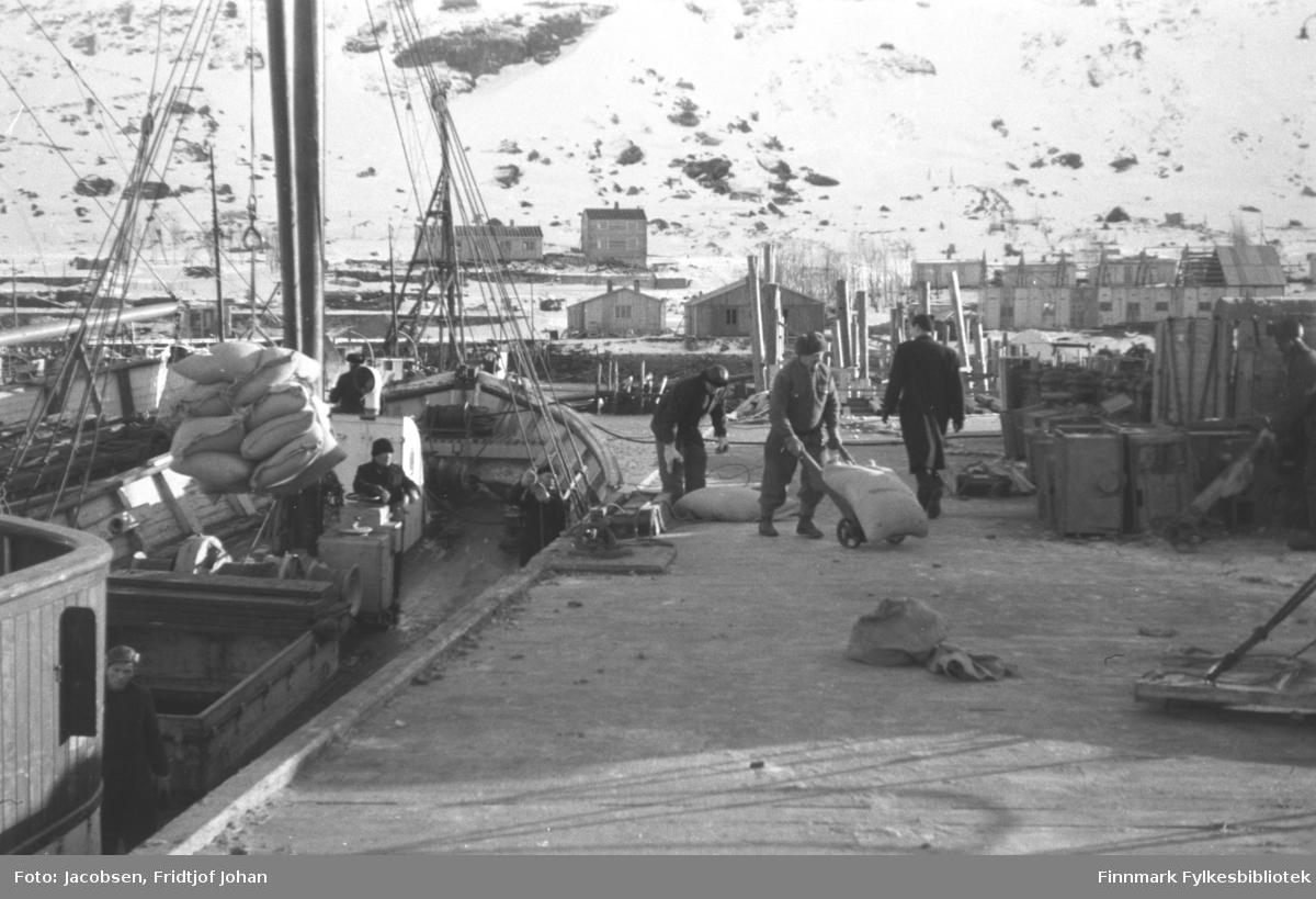 Nissenkaia i Hammerfest. Forsyninger strømmer inn vinteren 1945-46. Mannen som går med ryggen til er Ragnvald Jacobsen. Tre andre menn er i ferd med å losse fraktebåten som ligger ved kai. En fjerde står ved lasterommet, nede til venstre på bildet. Til høyre på bildet står endel trekasser og i bakgrunnen har noen brakker blitt satt opp og noen i ferd med å bli satt opp. Det snødekte fjellet i bakgrunnen er Salen