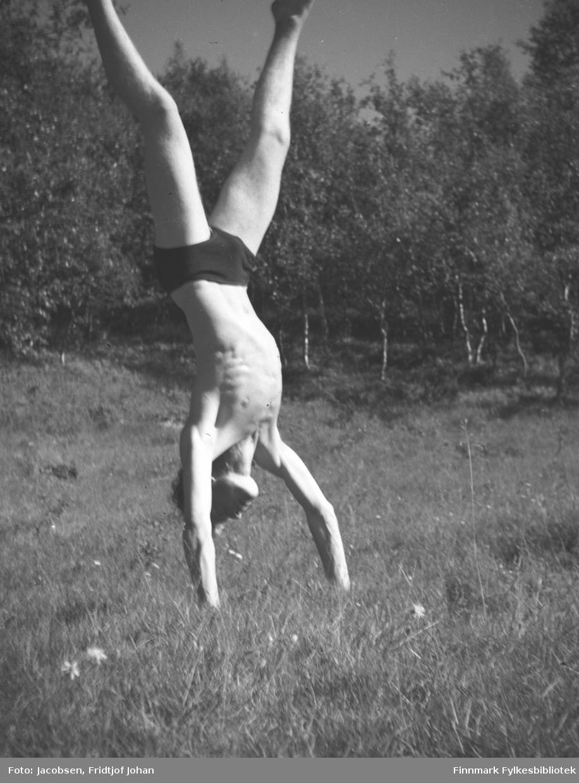 En ung mann som går på hendene i en gresskledt eng. Det kan være Fridtjof Jacobsen eller en av hans kamerater. Mannen har en mørk shorts på seg. Tett med løvtrær står i bakgrunnen.