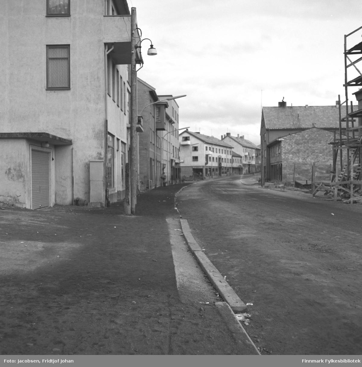 Strandgata i Hammerfest. Bygningen til venstre på bildet er Shellgården, tredje hus fra venstre er Finnmarkens Privatbank, DNB i dag, fjerde bygg på venstre side er G. Hagen og femte er Finnmark Dagblad og siste bygg på bildet er Lingengården. På høyre side er Samvirkelaget under bygging. Bygning nummer tre på høyre side er Finnmarksbo. Strandgata har grusdekke og el-stolper står med jevne mellomrom langs fortauet.